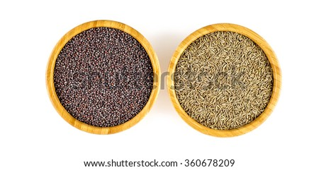 Bowls of black mustard seeds and cumin seeds in an overhead shot against white background. - stock photo