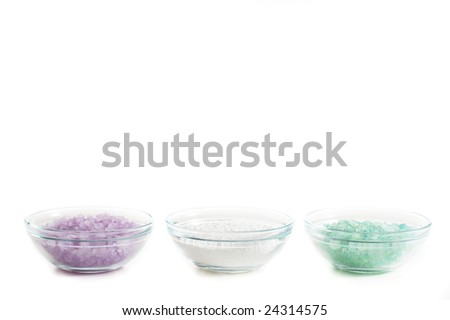 Bowls of colorful bath salt against a white background.