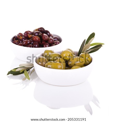 Bowls of green and black olives, in a white ceramic bowls with olive branch, over white background with reflection. - stock photo