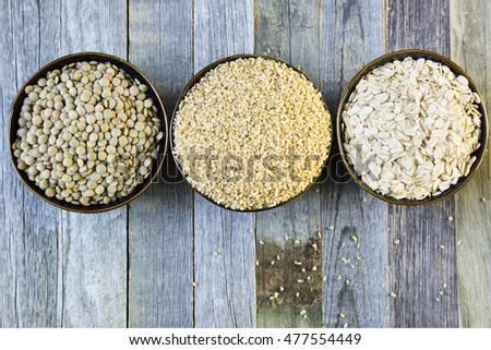 Bowls of lentils, bulgur and rolled oats in a row viewed from above on an old wooden table.