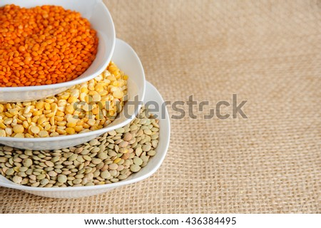 Bowls of various legumes (red turkish lentils, yellow indian lentils, green lentils) on rustic burlap background - stock photo