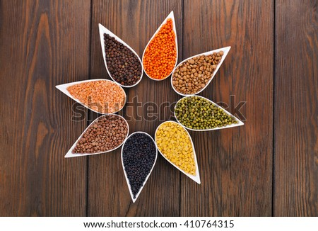 Bowls of various lentils on a wooden background - stock photo