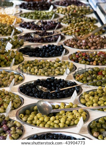 Bowls of various olives for sale at a market - stock photo