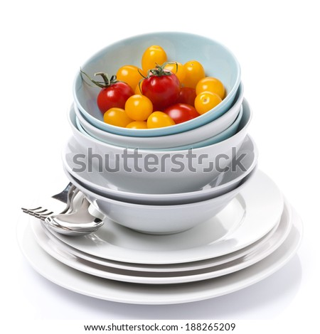 bowls, plates, cutlery and cherry tomatoes, isolated on white - stock photo