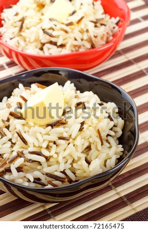 bowls with cooked rice and butter on bamboo napkin - stock photo