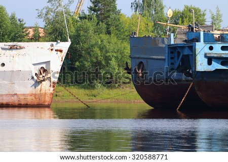 Bows of rusty cargo ships and lowered anchors on river at summer day - stock photo