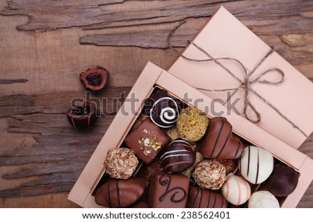 Box filled with chocolates on wooden rustic background - stock photo