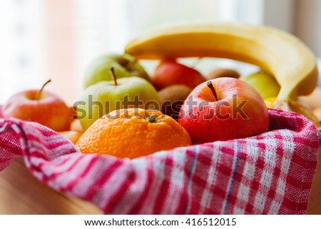 Box full of fresh fruits. Fruit harvest - apples, oranges, lemon, kiwi, banana. Rustic background.
