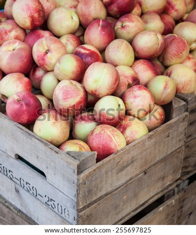 Box full of ripe nectarines offered at market stall - stock photo