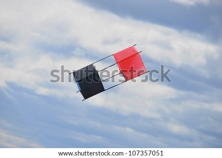 Box kite in red and black flying on the sky