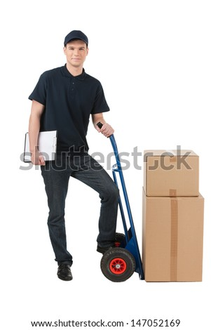 Box moving. Cheerful young deliveryman leaning on the cart with boxes on it while isolated on white - stock photo