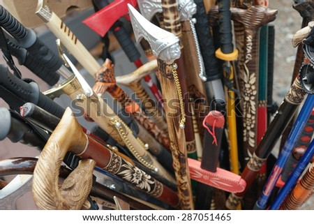Box of assorted decorative walking sticks or canes with ornamental handles in different shapes, some hand carved wood, displayed in store for purchase - stock photo