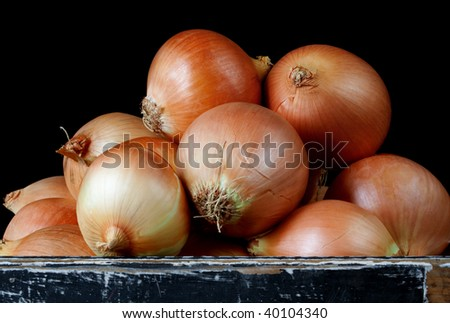 Box of brown onions, over black background.