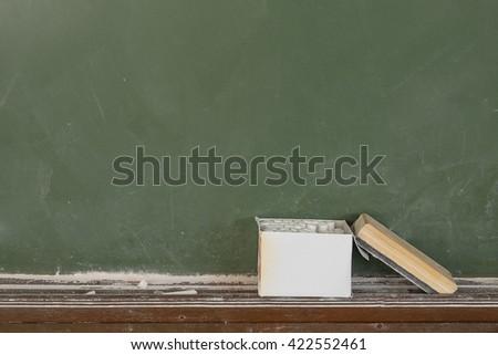 Box of chalk and blackboard eraser board background. - stock photo