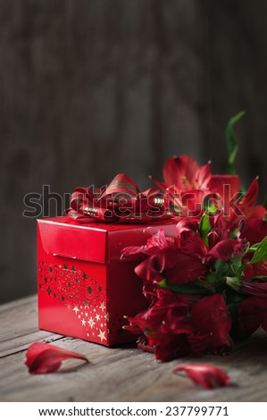 box of chocolate truffles with red flowers on wooden background