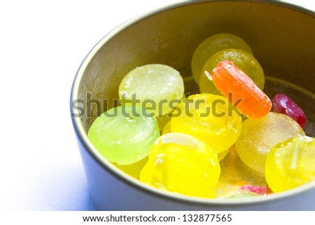 Box of colored candies on white background