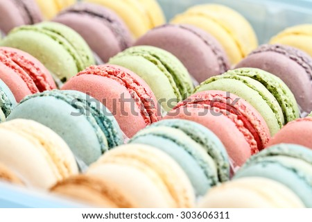 Box of fresh colorful macarons. Extreme shallow depth of field with selective focus on center macarons. - stock photo