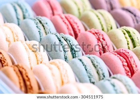 Box of fresh colorful macarons. Extreme shallow depth of field with selective focus on center blue macaron. - stock photo