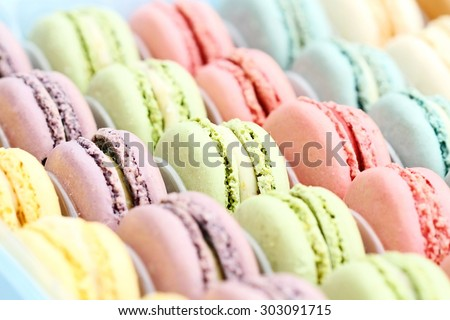 Box of fresh colorful macarons. Extreme shallow depth of field with selective focus on center green macaron. - stock photo
