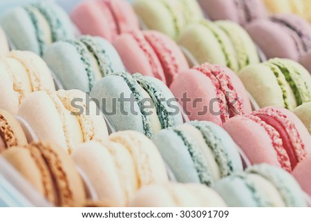 Box of fresh colorful macarons with vintage tones. Extreme shallow depth of field with selective focus on center blue macaron. - stock photo