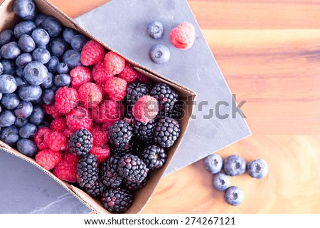 Box of fresh seasonal autumn berries with blueberries, blackberries, and raspberries displayed in a punnet on a wooden table fresh from the farmers market, with copy space - stock photo