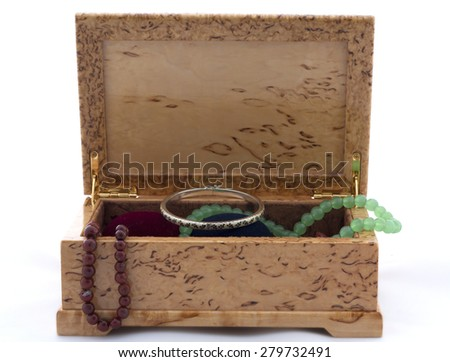 Box of karelian birch with jewels on white