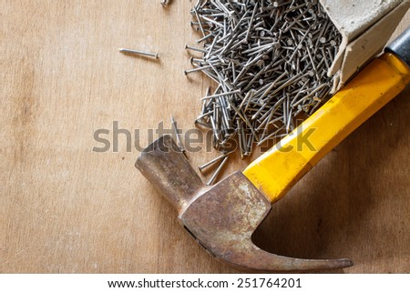 Box of old metal nails with hammer on wood background - stock photo