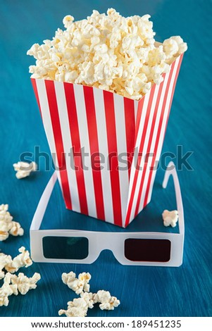 Box of popcorn and 3D glasses on blue background