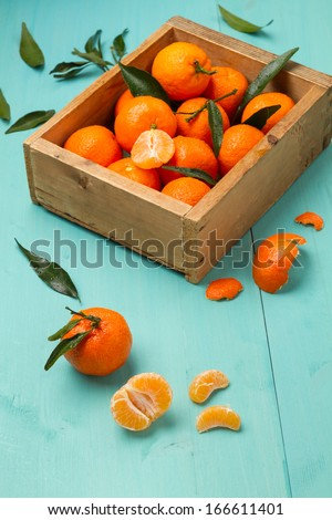 Box of tangerines on a turquoise kitchen table - stock photo