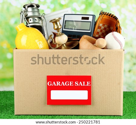 Box of unwanted stuff ready for a garage sale, on green grass - stock photo