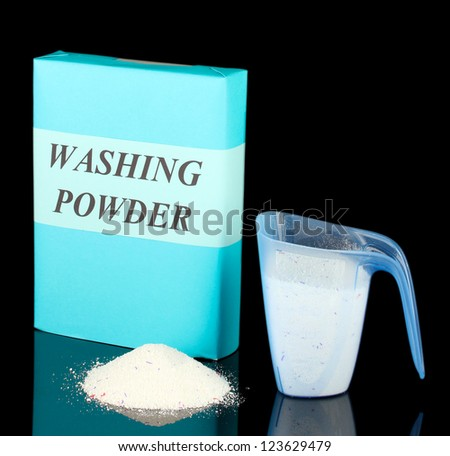 Box of washing powder with blue measuring cup, isolated on black - stock photo