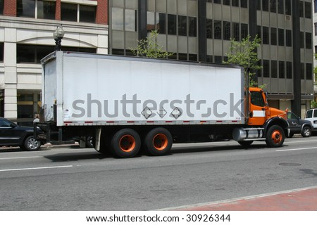 Box truck driving down the street - stock photo