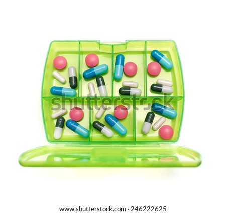Box with a weekly dosage of various drugs on a white background. - stock photo
