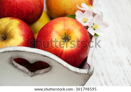 box with apples and apple tree blossoms  on a wooden table