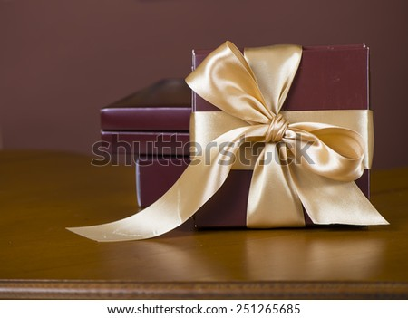 Box with candies and golden tape on wooden background