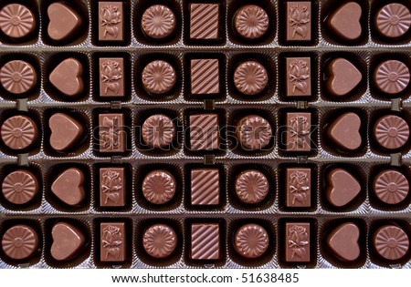 Box with chocolate candies' rows - stock photo