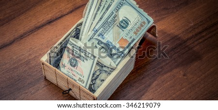 Box with dollar bills on wooden background. toned photo