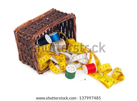 Box with measuring tapes and spools of thread on a white background. - stock photo