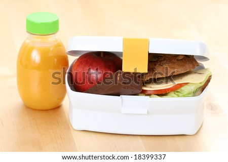 box with sandwich apple and chocolate and bottle of juice - stock photo