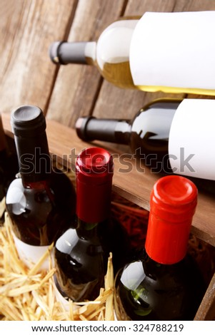 Box with straw and wine bottles on wooden background - stock photo