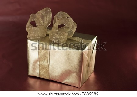Box wrapped in golden paper with a handmade bow on top.  On a background of shiny red paper.
