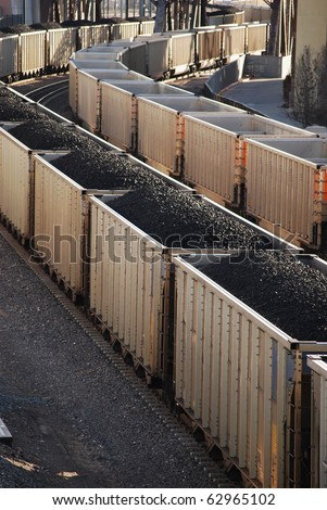Boxcars filled with black coal on a long train. Power and energy production that contributes to global warming. - stock photo