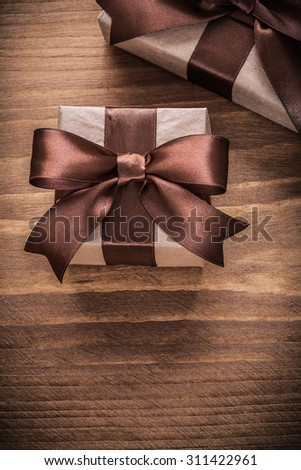 Boxed gift containers with brown ribbons on vintage wooden board.