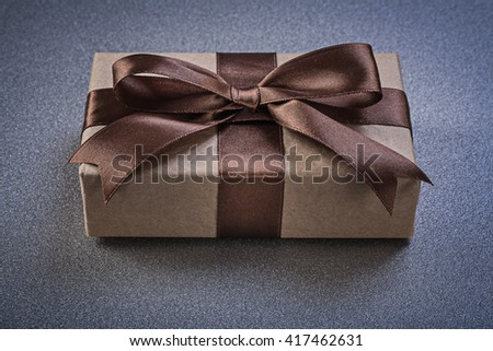 Boxed gift with brown bow on grey background top view celebrations concept. - stock photo