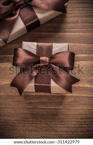 Boxed present containers with brown ribbons on vintage wooden board.