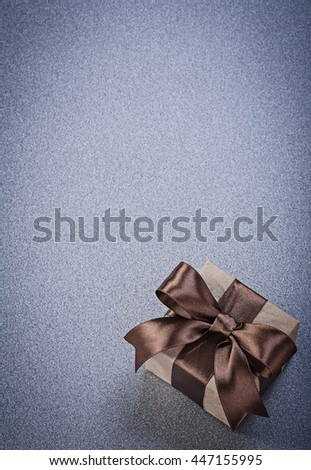 Boxed present in brown paper on grey background celebrations concept.