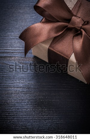 Boxed present in wrapping paper on vintage wood board copyspace.