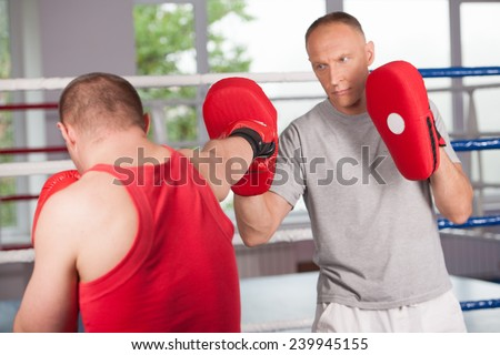 boxer and his coach doing some sparring in ring. Boxer and his coach practicing some moves