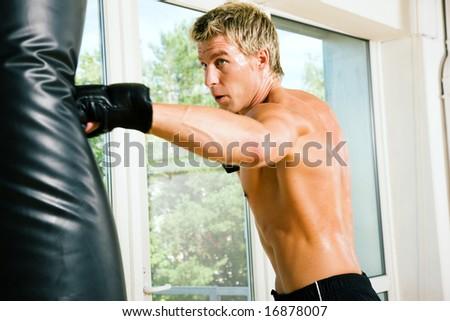 Boxer hitting the sandbag hard - stock photo
