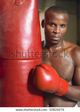 Boxer holding punching bag, portrait - stock photo